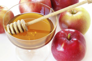Whole apples and bowl of honey